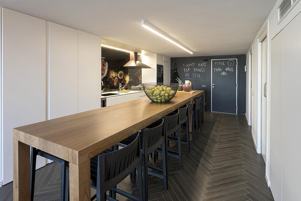 Diseño-vivienda-loft-cocina-armariada-blanca-mesa-isla-tiovivo